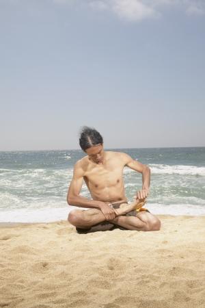 determines: Giovane uomo seduto a gambe incrociate sulla spiaggia
