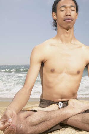 determines: Giovane uomo seduto sulla spiaggia meditando LANG_EVOIMAGES