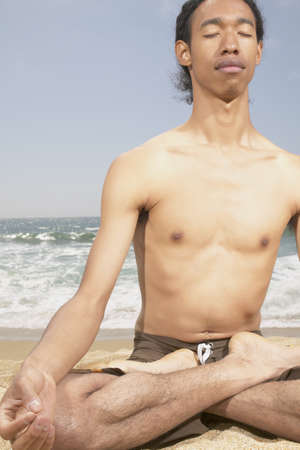 determines: Young man sitting on the beach meditating