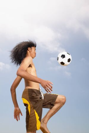 Low angle view of a young man playing football on the beach Banco de Imagens