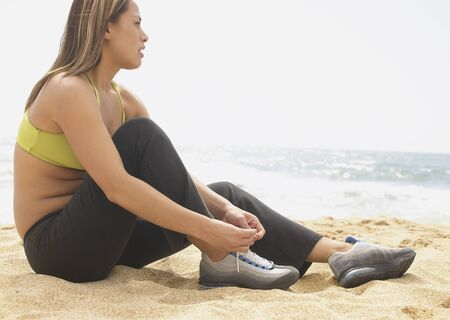 Side profile of a young woman sitting at the beach