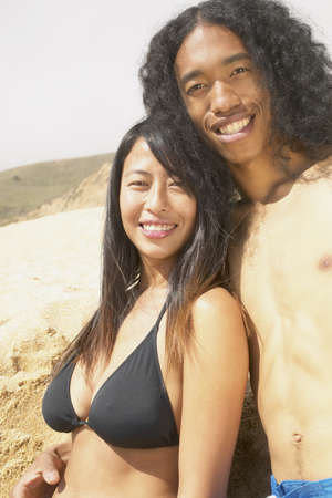 anecdote: Young couple standing at the beach holding each other