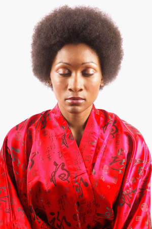 well beings: Young woman in a red kimono robe meditating