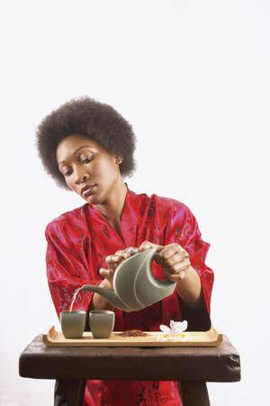 pragmatism: Young woman pouring green tea