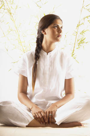 pragmatism: Young woman sitting on the floor meditating LANG_EVOIMAGES