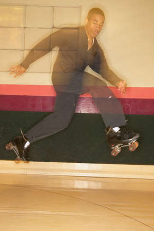 Man jumping on roller skates at a roller skating rink Stock Photo