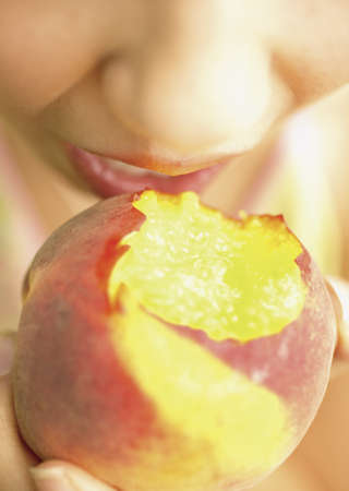 Young woman eating a peach
