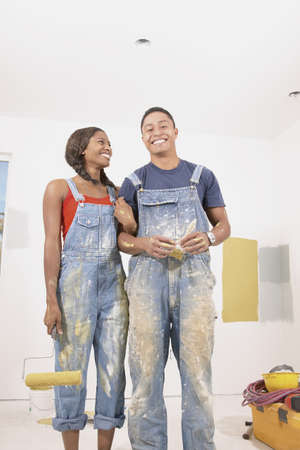 hauteur: Young couple standing with paint rollers