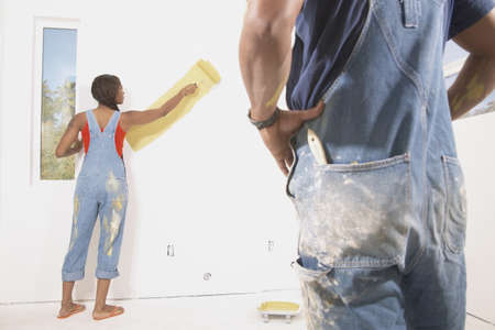 Rear view of a young couple painting a wall Stock Photo - 16045624