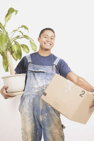 way of behaving: Portrait of mid adult man holding box and vase