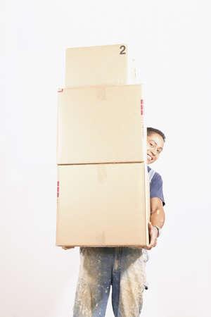 mid adult man: Hombre de mediana edad que lleva una pila de cajas