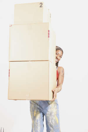 hauteur: Portrait of a young woman carrying a stack of boxes