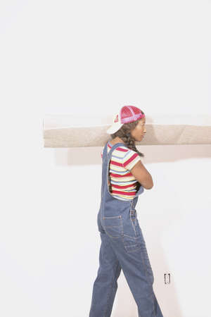 joyousness: Young woman carrying a carpet on her shoulder