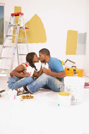 anecdote: Couple sitting on the floor kissing each other LANG_EVOIMAGES