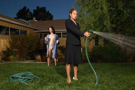 Young woman watering the lawn with a hose Stock Photo - 16045632