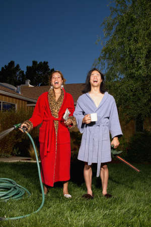 hauteur: Young couple wearing bath robes standing on a lawn