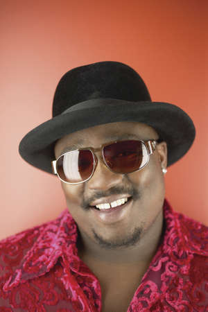defuse: Portrait of a man smiling wearing sun glasses and a hat LANG_EVOIMAGES