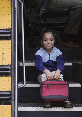 zapatos escolares: Chica joven sentado en los escalones del autobús escolar LANG_EVOIMAGES