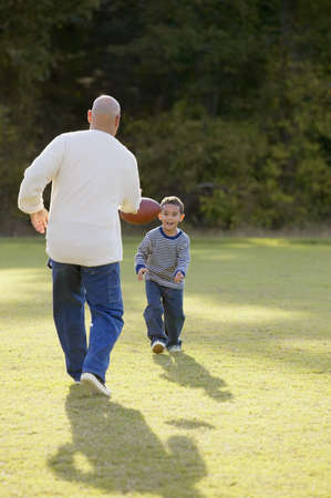running pants: Father playing rugby with his son in a park LANG_EVOIMAGES