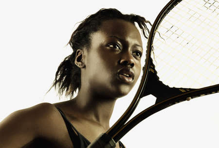 tennis racket: Low angle view of a young woman with a tennis racket