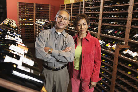 Portrait of a mature man with a young woman smiling in a wine store Stock Photo - 16045811