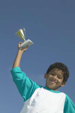 low prizes: Retrato de un joven sosteniendo un trofeo LANG_EVOIMAGES