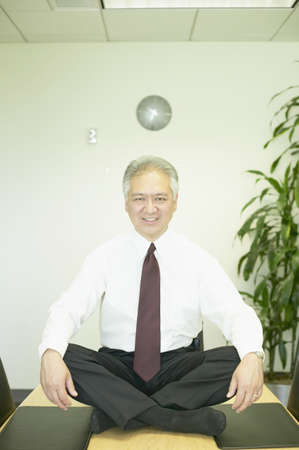 knee bend: Mature businessman sitting on the floor with eyes closed