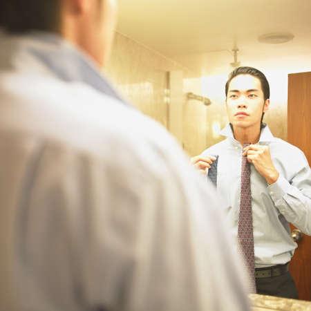bathroom mirror: Young businessman tying his tie
