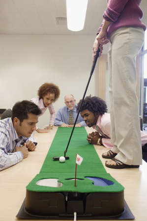 rolled up sleeves: Colleagues playing golf in a conference room