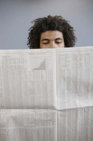 jamaican ethnicity: Young man reading a newspaper LANG_EVOIMAGES