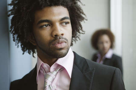jamaican ethnicity: Close-up of a businessman with a businesswoman standing behind him
