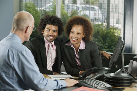 jamaican ethnicity: Two businessmen and a businesswoman in a meeting LANG_EVOIMAGES