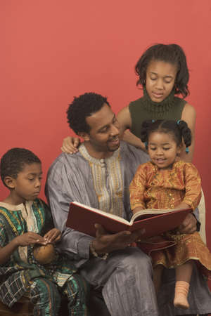 kwanzaa: Father with his two daughters and son reading a book