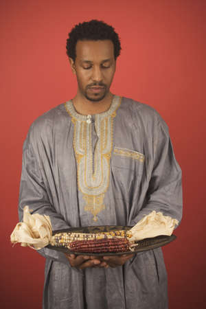 kwanzaa: Mid adult man holding Indian corn in a plate LANG_EVOIMAGES