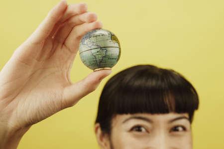 el mundo en tus manos: Primer plano de una mujer joven sosteniendo un globo en la mano