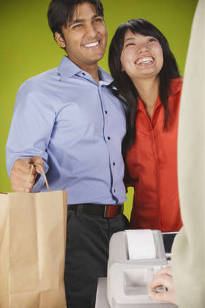 Young couple standing at a checkout counter smiling Stock Photo - 16046018