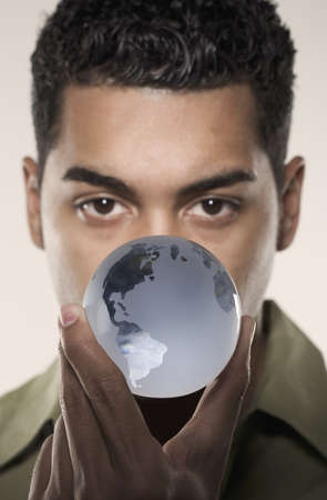world at your fingertips: Young man holding a glass globe