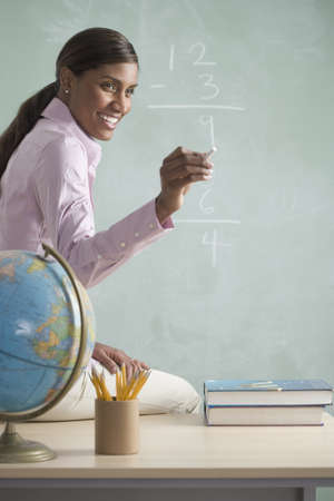 Side profile of a teacher sitting on a table in front of a blackboard Stock Photo - 16046079