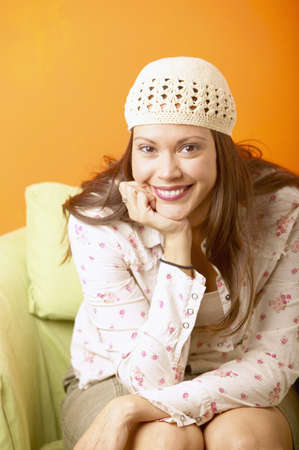 Young woman sitting on a couch smiling