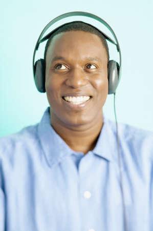 mid adult man: Mediados de adultos hombre vestido con auriculares sonriente