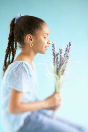 children's wear: Side profile of a young girl smelling flowers