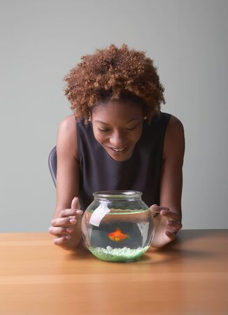 Mid adult woman looking at a fishbowl smiling