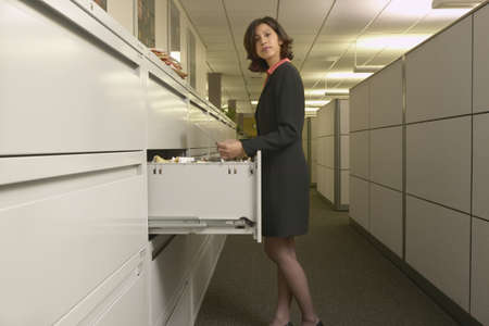 Young woman standing in front of a filing cabinet LANG_EVOIMAGES