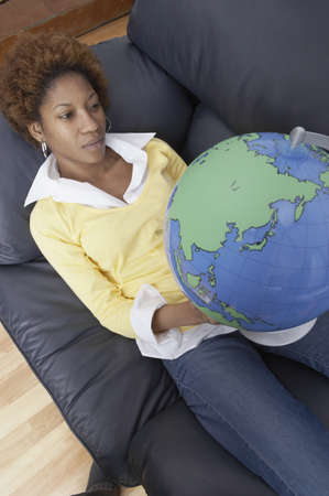 world at your fingertips: High angle view of a mid adult woman looking at a globe