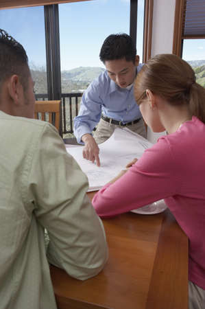 Architect with a young couple looking over blueprints Stock Photo - 16046267
