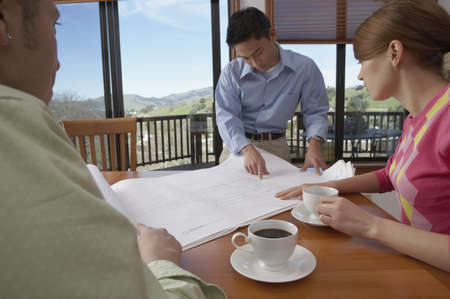 Architect with a young couple looking over blueprints Stock Photo - 16046268