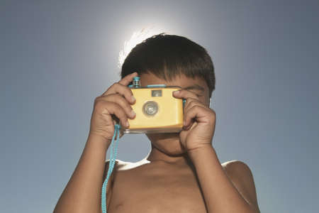 Low angle view of a boy looking through a toy camera Stock Photo - 16046286
