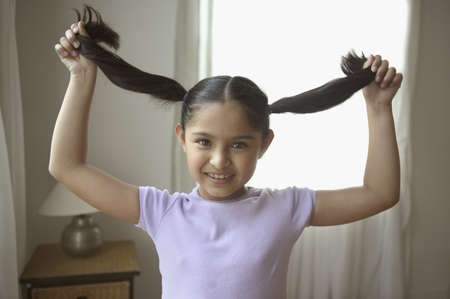 Portrait of a girl holding her pigtails Stock Photo - 16046369