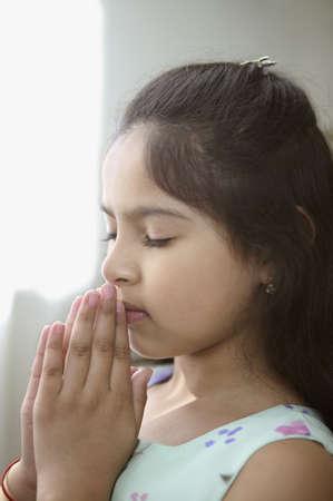 niño orando: Perfil lateral de una niña rezando LANG_EVOIMAGES