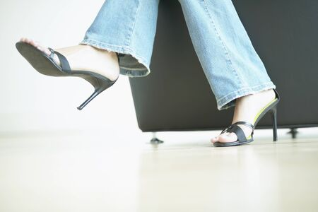 low section view: Low section view of a woman in high heel shoes and jeans sitting on a couch